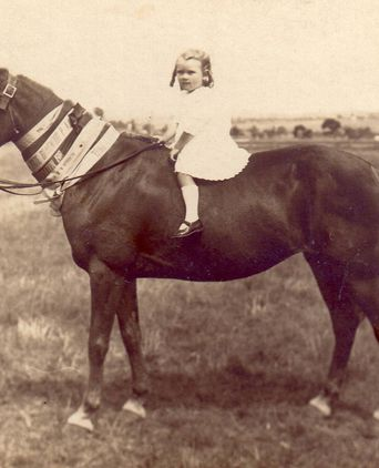 Hilda's horse showing her winning Show ribbons.  The child is her daughter Gladys.