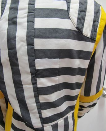 Patch repair over tear on back of jacket below the third horizontal stripe