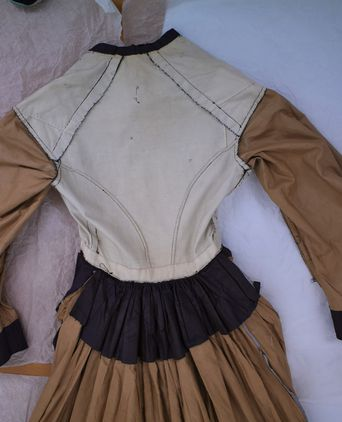 Inside view of back bodice and skirt. Bodice mounted on medium weight duck canvas. Sleeves and skirt are mounted in the same tan cotton fabric