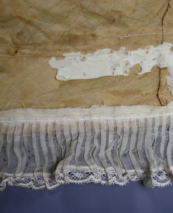 Underside of dress train where wear and insect damage is evident on the woollen brush hem.