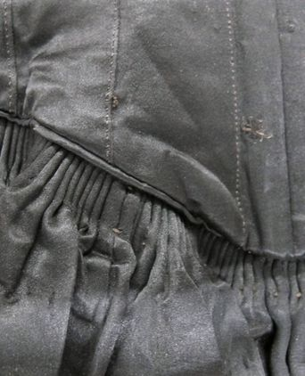 Pleating and repair detail at center-front waist
