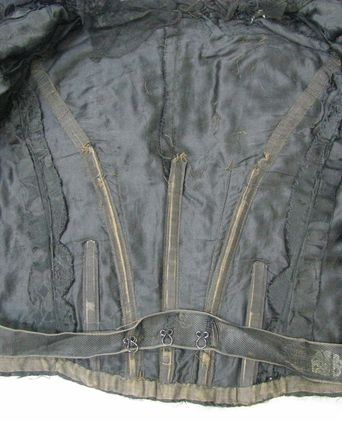 Inside jacket showing lining alterations, boning and maker's stamp on waistband