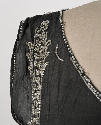 Close up of missing beadwork around the neckline