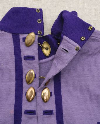 Close up of brass closer and caplet-shaped buttons down back