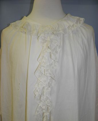 Machine lace is stitched to the ruffled collar and  around centre front opening