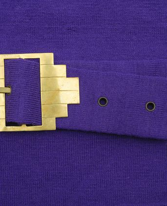 Close up of self belt with brass buckle trim