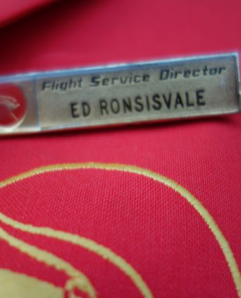 Flight Service Director badge worn directly above Qantas logo on left breast pocket
